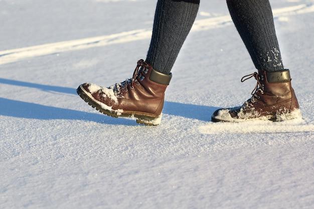 여성은 겨울에 신선한 눈 위를 걷는 부츠에 뒤쳐져 있습니다. 겨울 신발의 근접 촬영입니다.