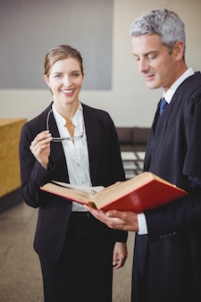 Female lawyer standing by male colleague