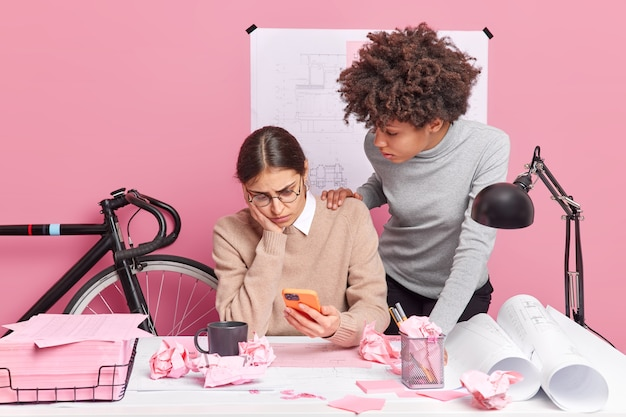Female leader of architectural project failed to make blueprints of building holds smartphone concentrated with puzzled expression at display her afro american partner tries to help gives advice