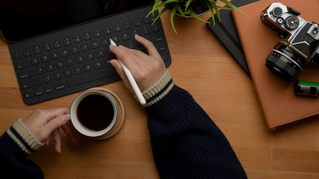 Female left hand holding coffee cup and right hand typing on tablet keyboard above worktable