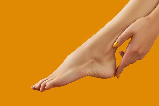 オレンジ色の背景に夏のネイルデザインと女性の脚と手