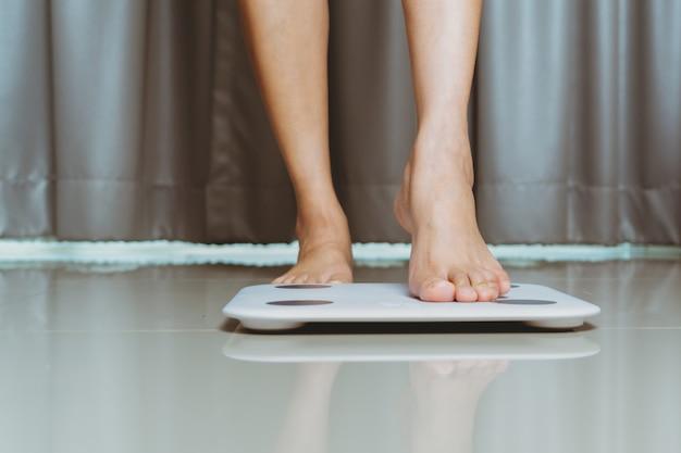 自宅で女性の脚が白い鱗を踏んでいる