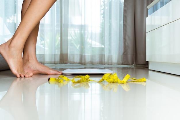 Женская нога наступает на белые чешуйки дома