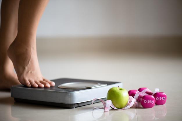 Женская нога наступая на весы с измеряя лентой, едой и концепцией спорта.