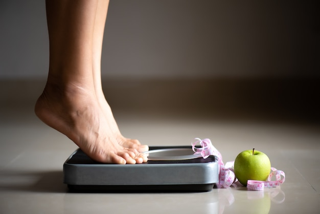 Female leg stepping on weigh scales with measuring tape and apple.