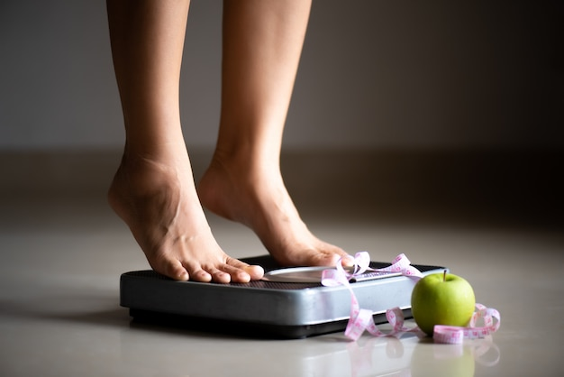 Female leg stepping on weigh scales with measuring tape and apple
