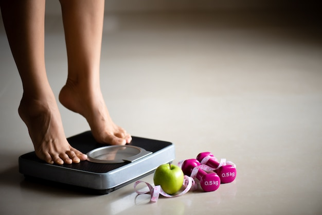 Female leg stepping on weigh scales with measuring tape and green apple