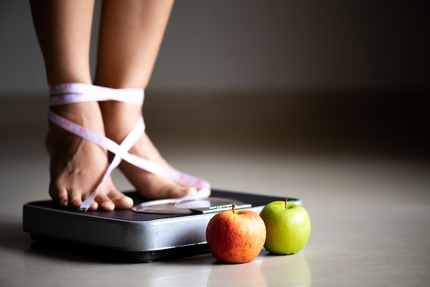 Female leg stepping on weigh scales with measuring tape and green apple.