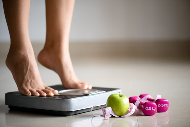 Female leg stepping on weigh scales with measuring tape
