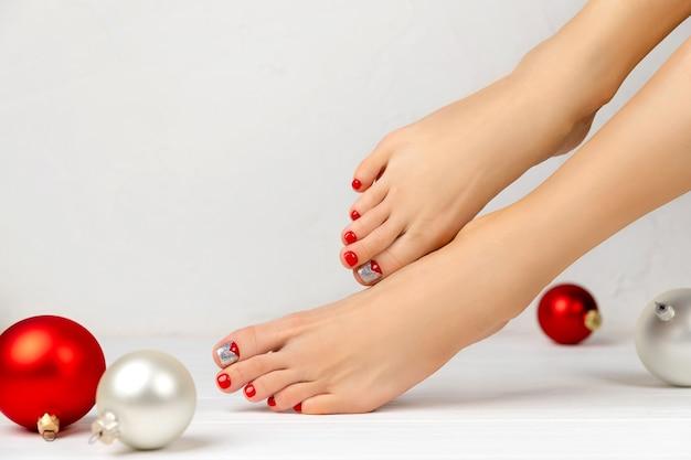 女性の足とクリスマスの飾り。マニキュアペディキュアビューティーサロンのコンセプト。