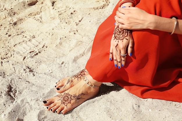 해변 모래 배경에 헤나 문신이 있는 여성의 다리와 손