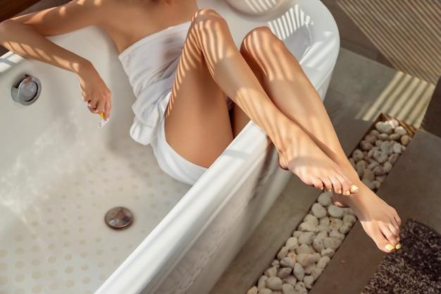 Женские ножки и руки с бритвой в ванной комнате с солнечным светом