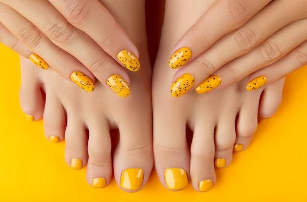 Женские ножки и руки с летним дизайном ногтей на оранжевом фоне