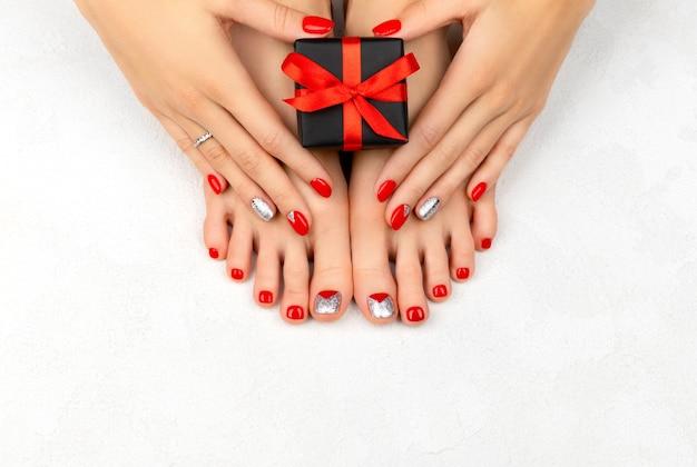 赤い爪を持つ女性の脚とハン。クリスマスセールのコンセプト。