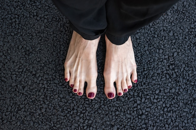 Female legs barefoot on black textured asphalt. road surface. selfi feet. top view