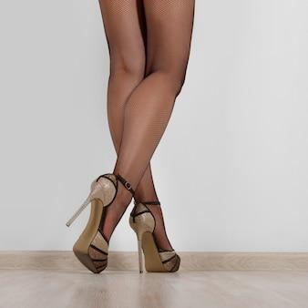 Female legs in black net stockings