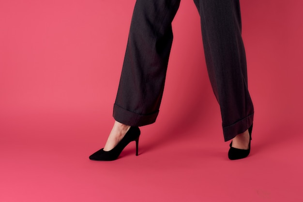 Female legs black shoes glamor luxury pink wall cropped view.