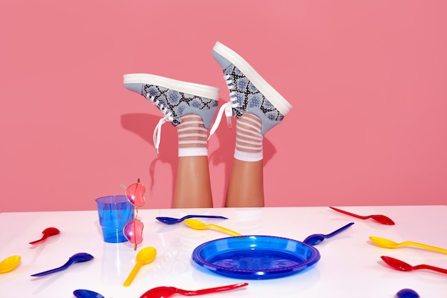 Female legs in blue sneakers sticking out above table