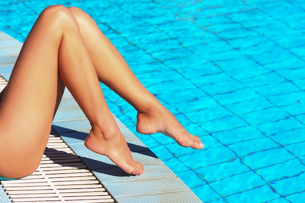 Female legs at blue water of swimming pool