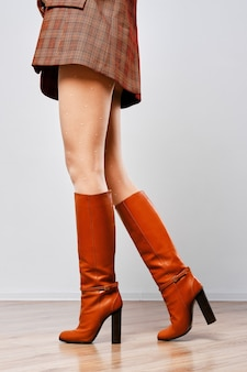 Female legs in brown boots and white tights with dot pattern