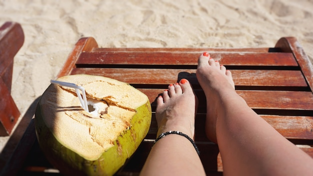 Female legs and coconut drink on the beach, travel and relax