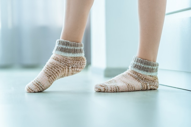 Female legs in cozy soft warm knitted winter socks at home