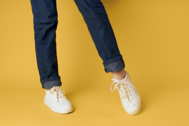 Female legs cropped view phasing white shoes modern style yellow background
