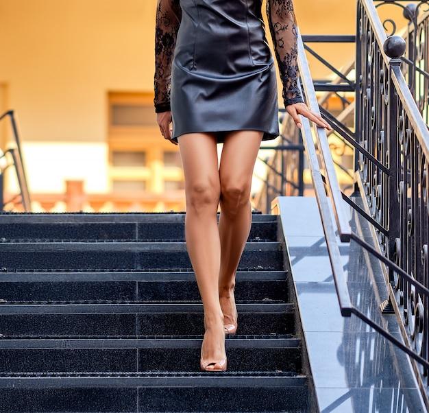Female legs descending the stairs