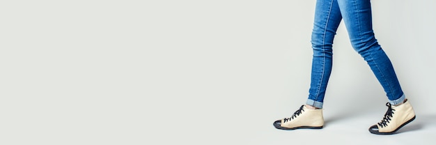 Female legs go in jeans and sneakers . banner