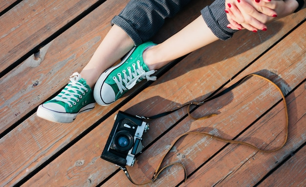 Female legs in hipster sneakers and retro camera on wooden surface outdoors, crop photos