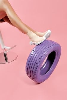 자동차 타이어에 기대어 베이지색 양말 운동화에 여성 다리
