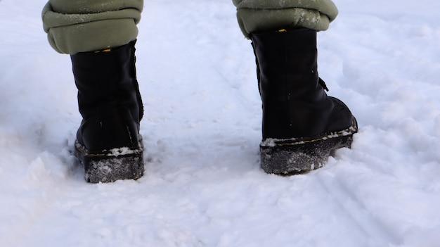 검은 부츠에 여성 다리, 겨울 눈 속에서 산책. 겨울 숲에서 카메라에서 멀리 걷는 활동적인 여자. 다리에 집중하세요. 신선한 눈과 함께 아름 다운 하얀 겨울 날씨입니다.