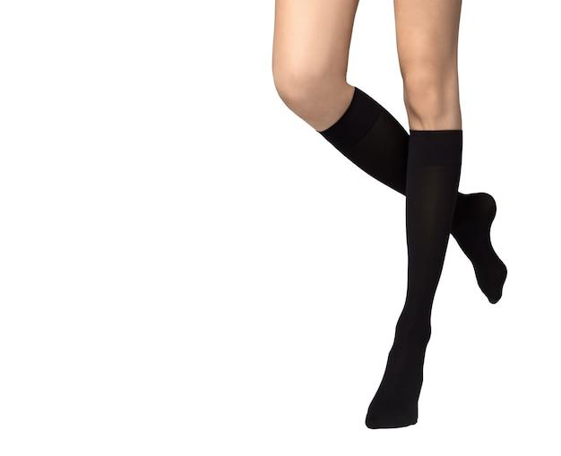 白い背景に黒い靴下を履いた女性の足