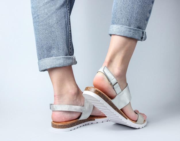 ブルージーンズと白の上を歩いてトレンディなレザーサンダルの女性の足。女性のスタイリッシュな夏の靴。ミニマルなファッション撮影。
