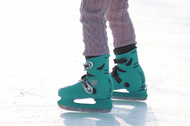 아이스 링크에서 블루 스케이트에 여성 다리입니다. 스포츠 및 엔터테인먼트. 휴식과 겨울 방학.