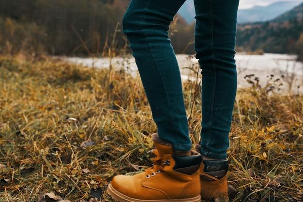 山の秋の自然のブーツとジーンズの女性の足