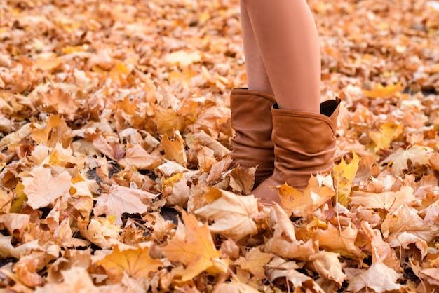 Женские ножки в коричневых сапогах. желтая листва под ногами. осенняя концепция