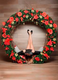 Женские ножки в елочных украшениях с книгой. девушка читает книгу на рождество