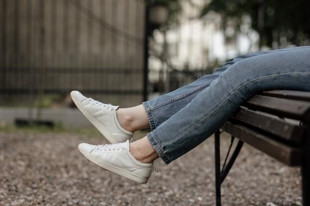 公園のベンチに座っている快適なカジュアルスニーカーの女性の脚。スニーカーのモックアップ。