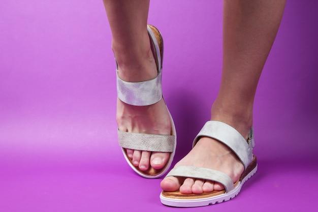 紫のファッショナブルなレザーサンダルで女性の足。夏の靴。