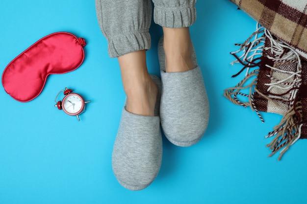 睡眠ルーチン アクセサリー付きの青地に灰色のスリッパを履いた女性の足