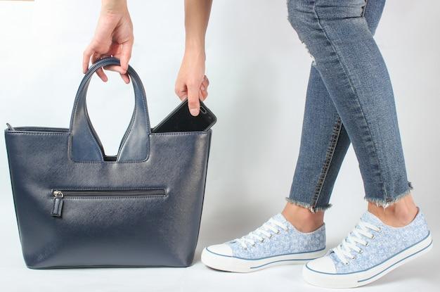 청바지와 운동화 여성 다리, 여자는 가죽 가방에 스마트 폰을 넣습니다