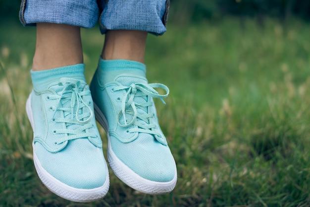 ジーンズやスポーツシューズの公園で緑の芝生の上の空気に浮かぶ女性の足