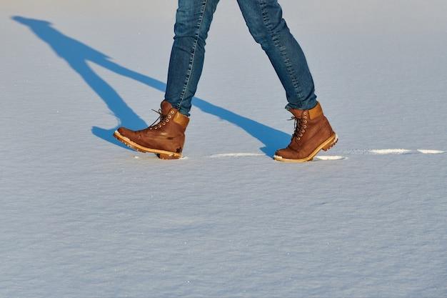 가죽 갈색 방수 부츠를 입은 여성 다리는 겨울 동안 신선한 눈에 하이킹을합니다. 캐주얼 패션, 트렌디 한 신발.