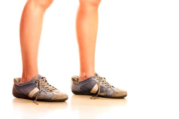 흰색 배경 위에 남자의 큰 신발에 여성 다리