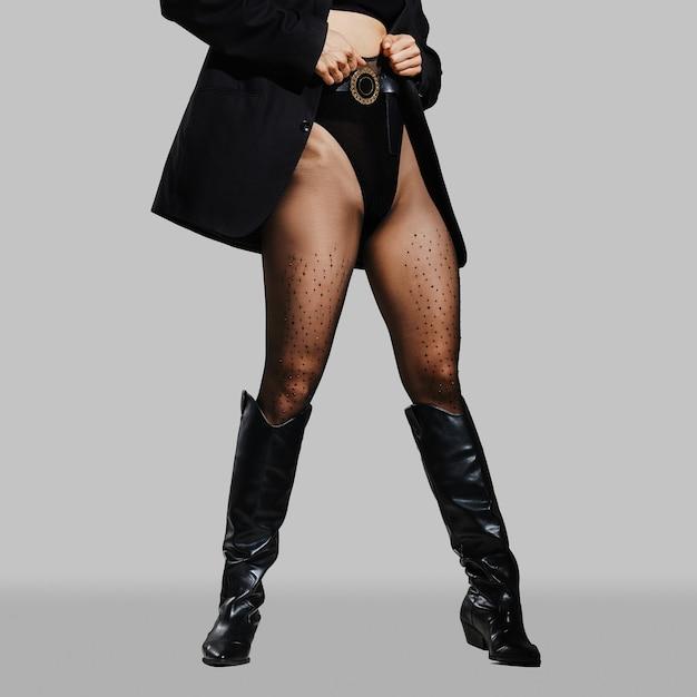 스튜디오에서 포즈를 취하는 팬티, 스타킹 및 가죽 승마 부츠 여성 다리