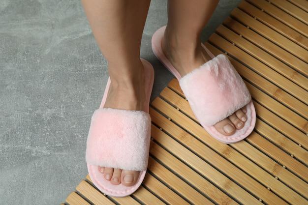 灰色の床に竹の上にピンクのスリッパを履いた女性の足