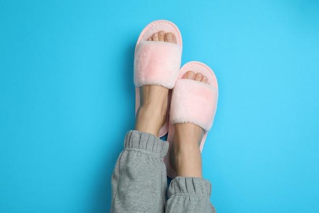 青地にピンクのスリッパを履いた女性の足