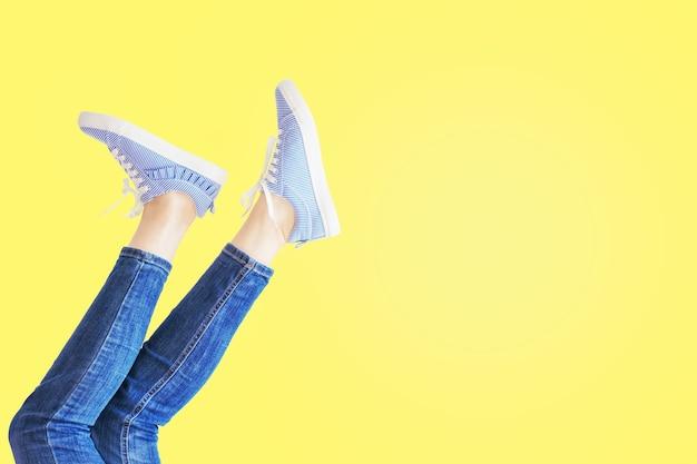 노란색 배경에 포즈에서 여성 다리입니다. 복사 공간이 있는 청바지와 줄무늬 운동화를 신은 여성의 발