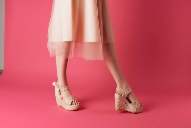 靴のドレスの女性の脚は、ピンクの背景のポーズをトリミングされたビュー